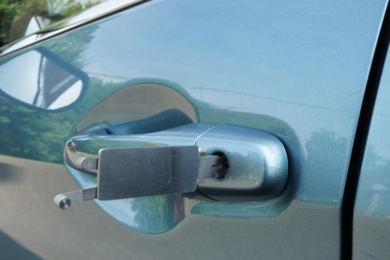 image of lock picks being used to unlock a car door lock