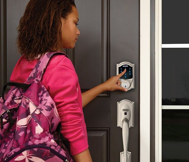 image of a woman typing her code into the keypad of a Schlage smart lock deadbolt
